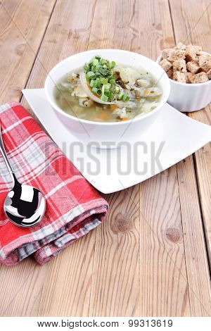 hot fresh diet vegetable soup with rye bread crackers over wood table on white ceramic stand
