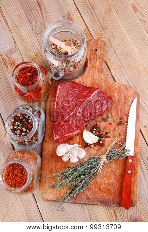 raw beef meat fillet with peppercorn and thyme and different spices in glass bottles ready to grill on wood figured aged board over table