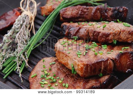 roasted beef meat on bbq pan with pepper and thyme isolated on white background