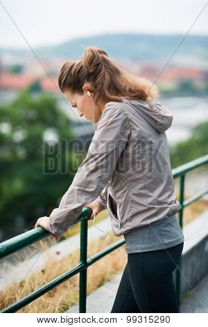 Woman Runner In Profile, Leaning Against Guardrail, Looking Down
