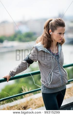 Woman Runner Stretching Using A Guardrail And Listening To Music