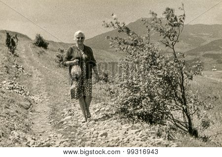 Vintage photo of woman walking in mountains, 1950's
