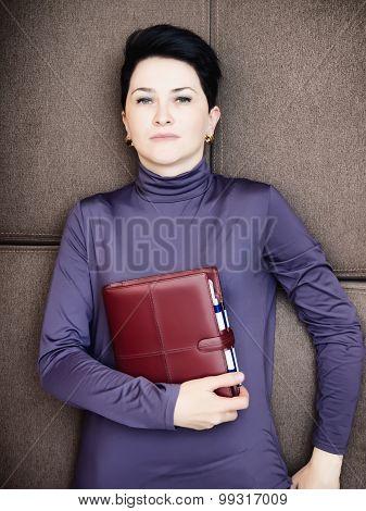 Sad businesswoman lies with personal organizer handheld and handbag on sofa