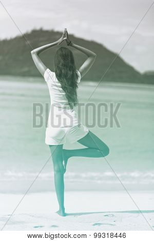 Rear View of Long Hair Woman Doing Yoga Activity at the Beach. Performing One Leg Balance with Hands Above the Head.