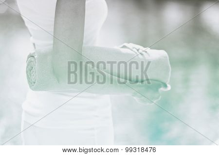 Close up torso view of a slender young woman standing poolside with a rolled towel against sparkling cool water in a wellness and spa concept