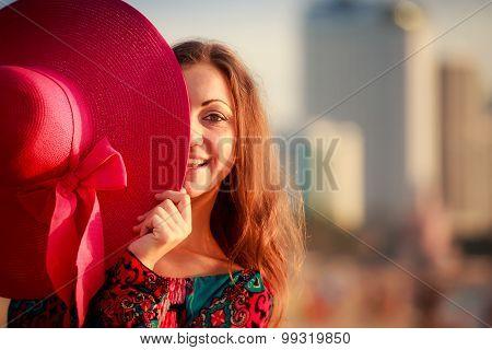 Brunette Girl Looks Out Of Big Red Hat On Defocused Background