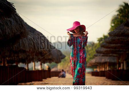 Slim Girl In Red Hat Looks Down Among Defocused Umbrellas