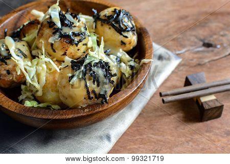 takoyaki on wooden table with chopsticks Japanese food