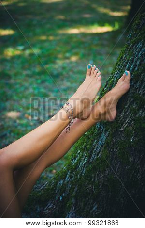 barefoot female legs with ankle bracelet, lean on tree, closeup, selective focus