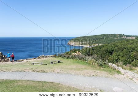 BORNHOLM, DENMARK - AUGUST 14: Tourists enjoy the sunny weather and walking along the cliffs on the Baltic Sea on 14 August 2015 on Bornholm Island near the Hammershus castle ruins, Denmark.