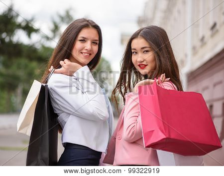 Two asian girl posing with shopping bags