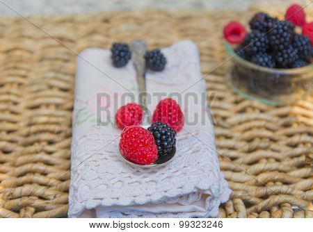 Raspberries and blackberries over lace napkin.
