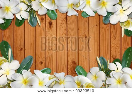 Frangipani flowers and leaf frame on brown wood floor background