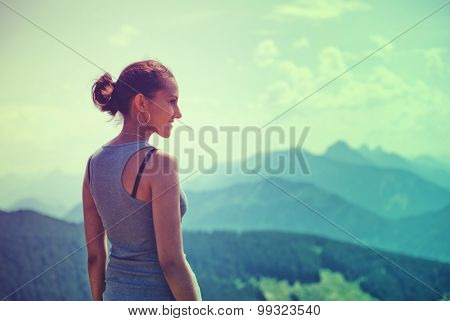 Attractive woman enjoying the beauty of nature standing on a mountain summit looking out over the alps and distant mountain peaks with the glow of the evening sun lighting up her face