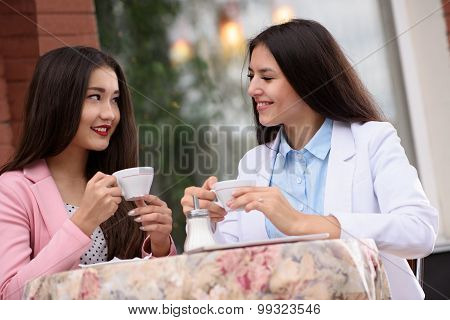 Two Asian business woman in outdoor cafe with coffee and having a conversation