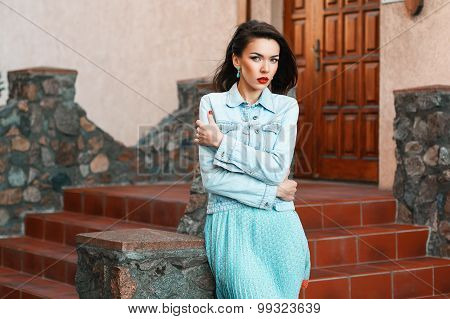 Young beautiful woman in denim dress standing and twisting stone steps near the house.