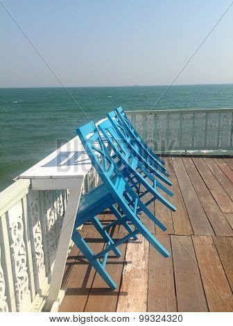 Blue chairs on white sea pier