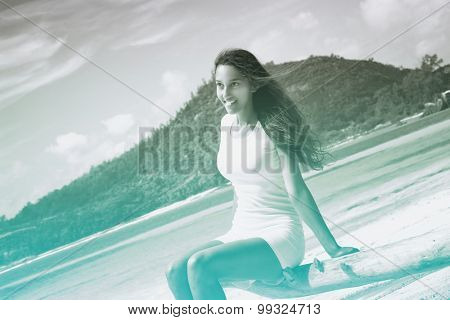 Close up Young Attractive Woman Wearing White Casual Outfit Sitting on Dry Tree Branch at the Beachfront.