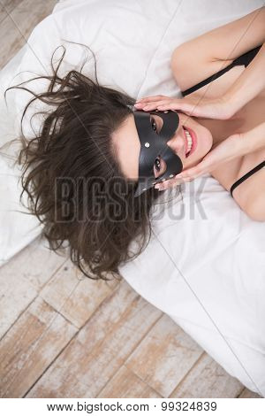 Playful beautiful brunette in a black leather mask