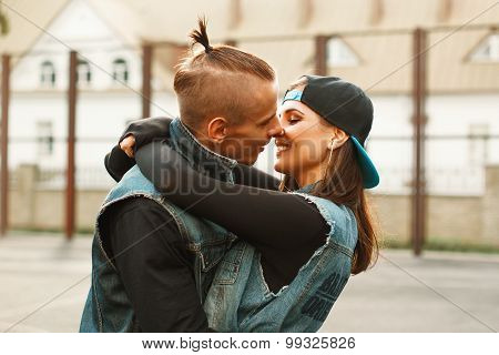 Young couple hugging and kissing at the stadium. Dancers in denim clothes.