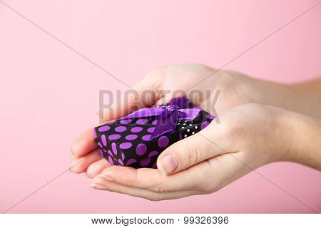 Female Hands Holding Gift Box On Pink Background