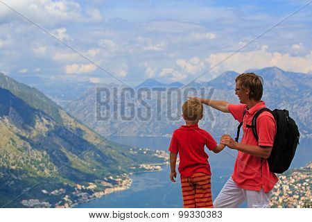 father and son looking at mountains in summer