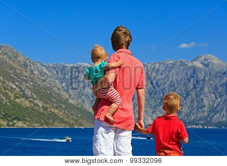 father with two kids on vacation in mountains