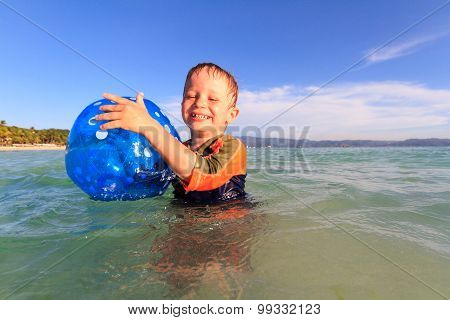 little boy playing ball in water