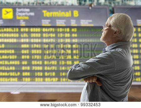 Senior on a background of departure board at airport