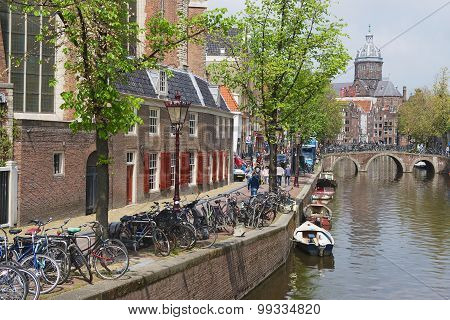 View to the canal with bicycles parked in Amsterdam, Netherlands.