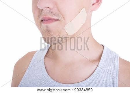 Close Up Of Medical Adhesive Plaster On Male Face Isolated On White