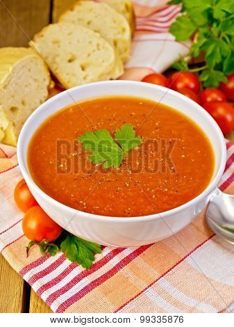 Soup tomato with bread on napkin and board