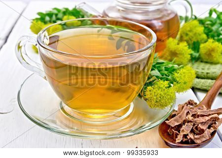 Tea of Rhodiola rosea in cup with spoon on board