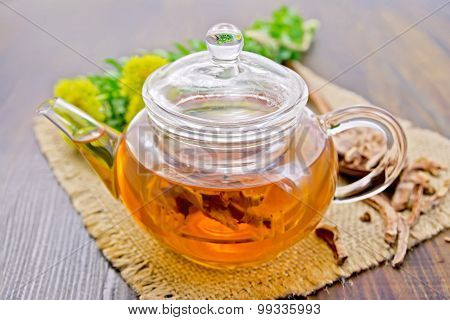 Tea of Rhodiola rosea in glass teapot on board