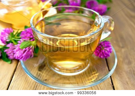 Tea with clover in cup and teapot on board