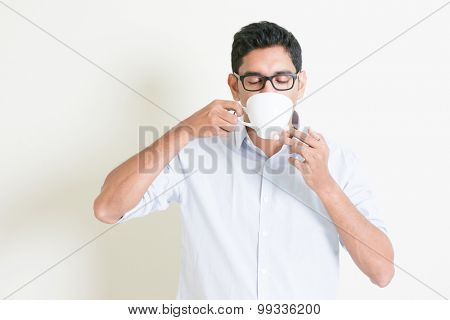 Portrait of handsome casual business Indian guy relax and drinking a cup hot coffee, standing on plain background with shadow, copy space at side.