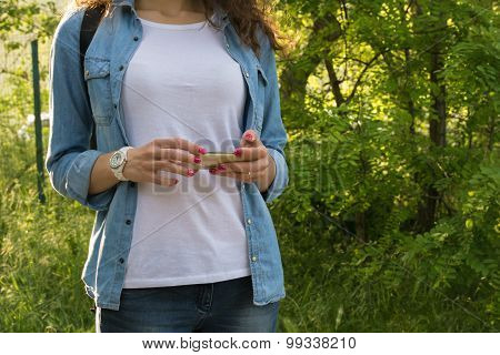 Young Woman Using A Mobile Phone During A Hike With A Backpack On Nature
