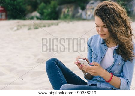 Young Pretty Girl In Denim Clothes Using A Mobile Phone On The Beach