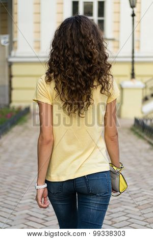 Attractive Slim Young Woman With Curly Brown Hair Is Walking On The Old European City