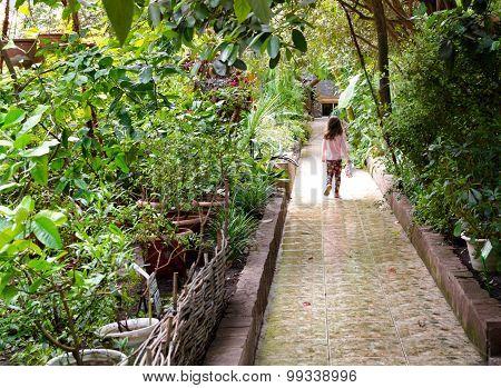 Young Girl Walking Along Tropical Stone Tile Path