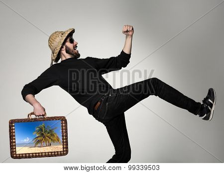 Young, attractive man  in sunglasses with  suitcase ready to travel