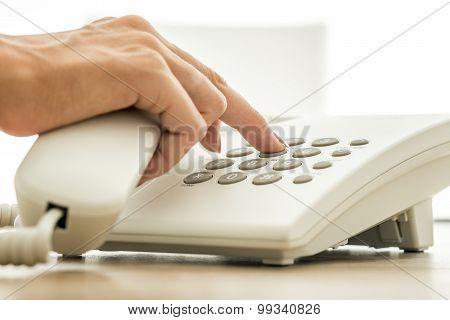 Closeup View Of Female Secretary Dialing A Telephone Number On White Landline Phone