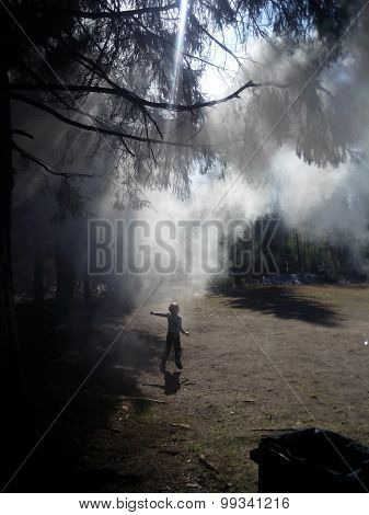 Small boy running through forest shrouded in smoke