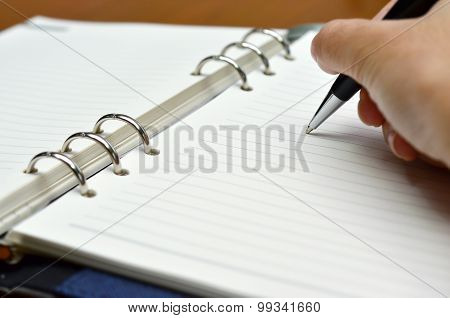Hand with a pen writing on white paper