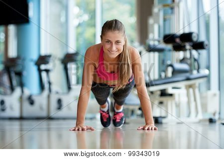 Gorgeous blonde woman warming up and doing some push ups a the gym