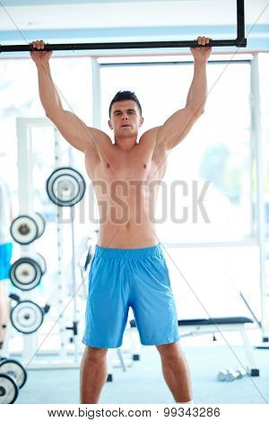 handsome young man in fitness gym lifting up and hanging while working on hands and back muscles