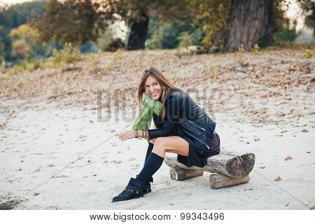 Beautiful Woman Sitting On A Bench At The Beach