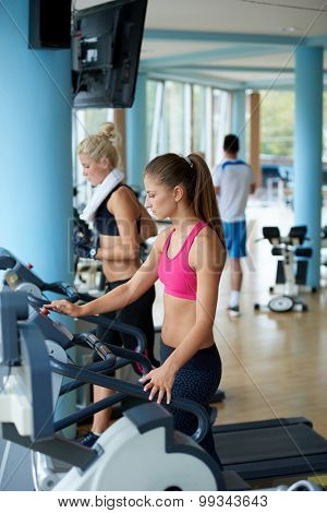 Beautiful group of young women friends  exercising on a treadmill at the bright modern gym