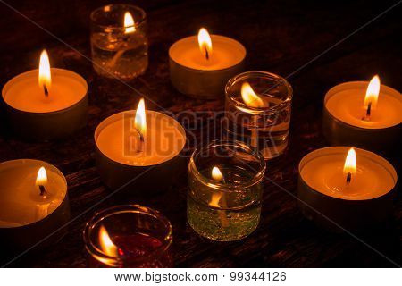 Burning Gel And Wax Candles On A Wooden Background