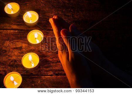 Man Praying Next To The Candles
